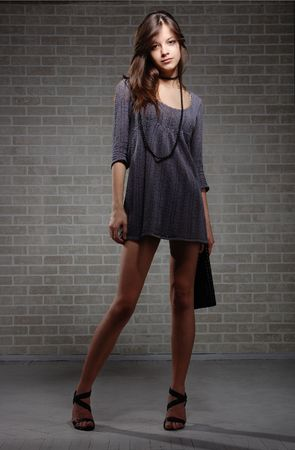Sexual brunette fashion model  in knitted dress on brick wall background  photo