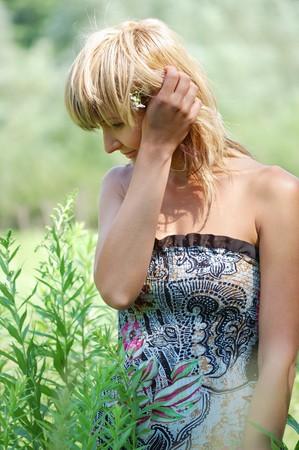 sundress: Beautiful blonde in sundress enjoys  unification with nature . Stock Photo