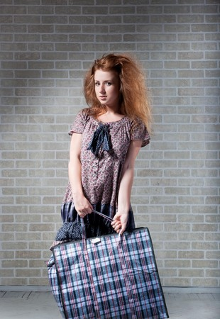 uncombed: Tired redhaired woman with shopping bag.  brick wall as background.