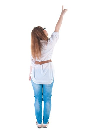 Young woman points at wall. The rear view . photo