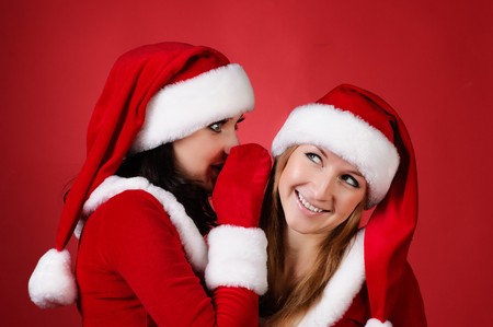 wo happy young Santa girl talking over red background . photo