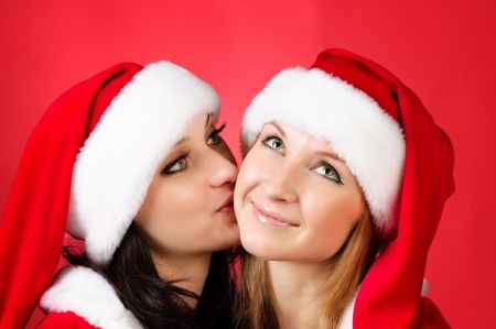 Two girl friends in christmass costumes on red. photo