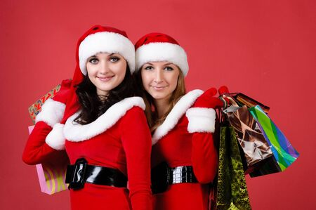 Two women in dressed as Santa, with shopping bags . on red background . photo