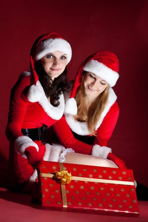 two woman in Santa costume opening christmas gift. on red photo
