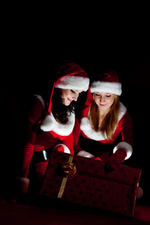 two woman in Santa costume opening christmas gift. on black . photo