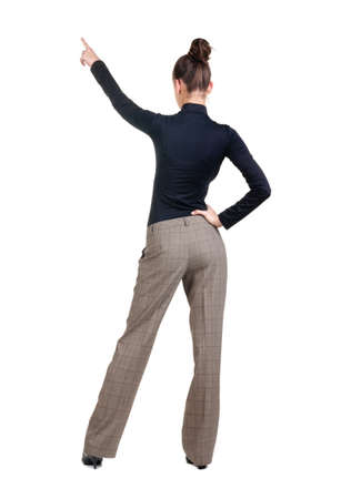 Beautiful young woman pointing at wall. Rear view. Isolated over white backrgound. Stock Photo - 8349465