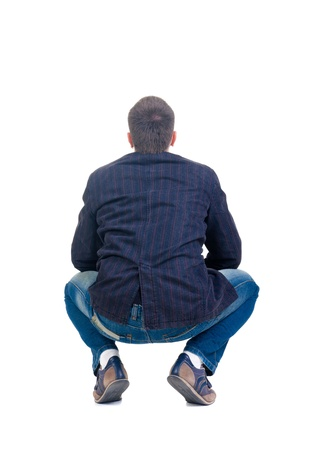 Sitting young man looking afar. Rear view. Isolated over white. photo
