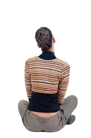 sitting young woman looks afar. Rear view. isolated over white. photo