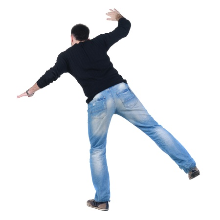 to stumble: Balancing young man in jacket. Rear view. Isolated over white. Stock Photo