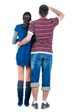 Young couple looks where that. Rear view. Isolated over white. photo
