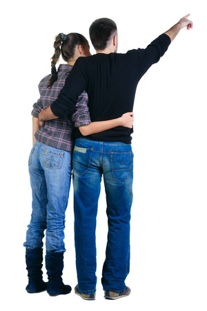 backside: Young couple pointing at wall. Rear view. Isolated over white background. Stock Photo