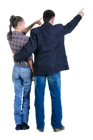Young couple pointing at wall. Rear view. Isolated over white background. photo