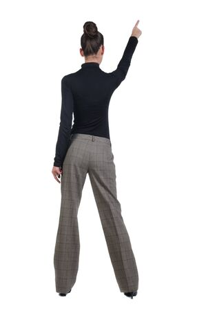 Beautiful young woman pointing at wall. Rear view. Isolated over white backrgound. Stock Photo - 8599371