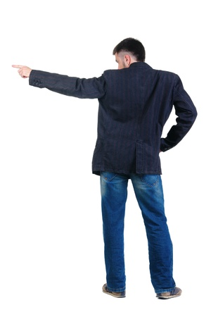 young man pointing at wall. rear view. Isolated over white . Stock Photo - 8599368
