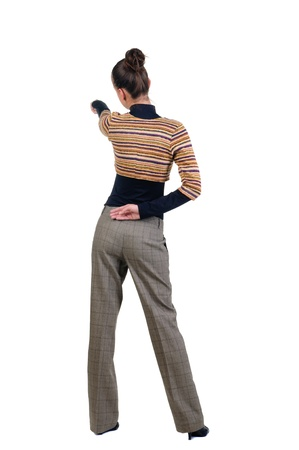 Beautiful young woman pointing at wall. Rear view. Isolated over white backrgound. Stock Photo - 8599381
