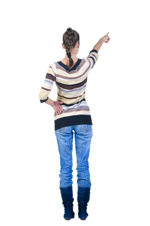 Beautiful young woman pointing at wall. Rear view. Stock Photo - 8665464