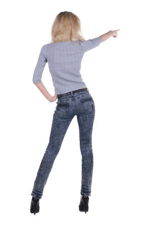 Beautiful young woman pointing at wall. Rear view. Stock Photo - 8999087