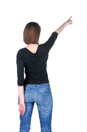 Beautiful young woman pointing at wall. Rear view. Isolated over white. Stock Photo - 9103676