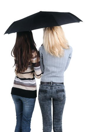 Two women under an umbrella. Rear view. Isolated over white. photo