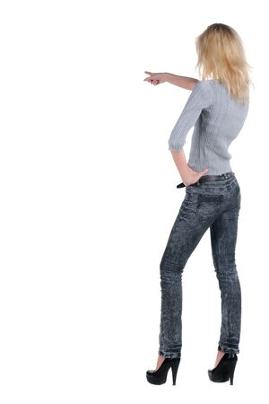 Beautiful young woman pointing at wall. Rear view. photo