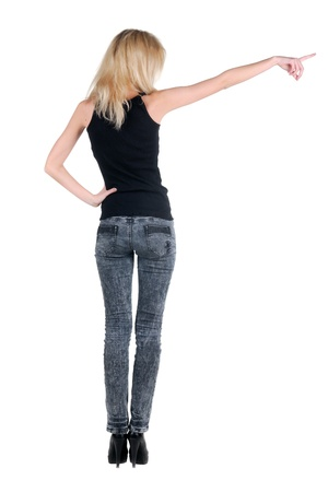 backside: Beautiful young woman pointing at wall. Rear view. Isolated over white. Stock Photo