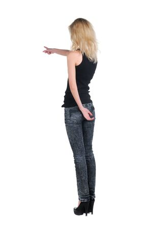 Beautiful young woman pointing at wall. Rear view. Stock Photo - 9258314