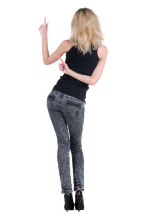 Beautiful young woman pointing at wall. Rear view. Isolated over white. Stock Photo - 9258346