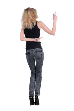 fingers on top: Beautiful young woman pointing at wall. Rear view. Isolated over white. Stock Photo