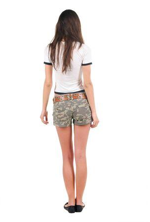 Belle jeune femme en shorts à la recherche au mur. Vue arrière. Isolé sur blanc.