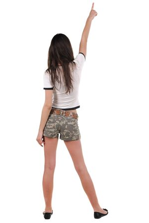 Beautiful young woman in shorts pointing at wall. Rear view. photo
