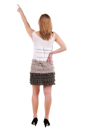 Beautiful young woman in dress pointing at wall. Rear view. Isolated over white. Stock Photo - 9999795