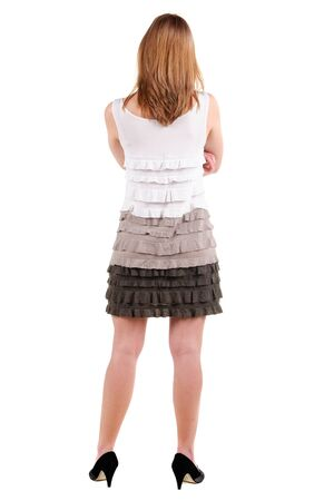 Beautiful young woman in dress pointing at wall. Rear view. Stock Photo - 9999796