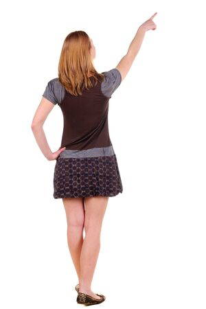 Beautiful young woman in dress pointing at wall. Rear view. Isolated over white. Stock Photo - 9999808