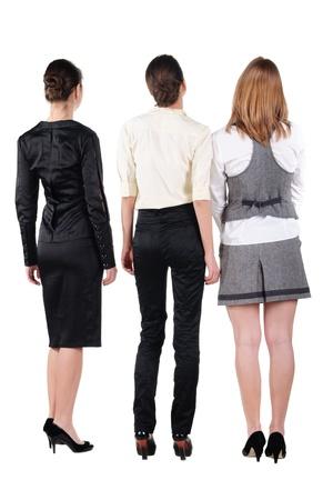 tre belle giovani bussineswoman guardando il muro. Vista posteriore. Isolato su bianco.