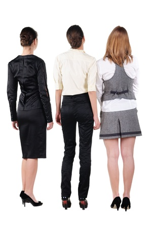 backside: three beautiful young bussineswoman looking at wall. Rear view. Isolated over white. Stock Photo