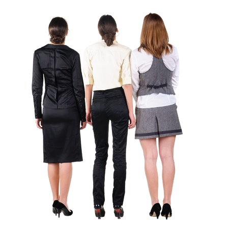 only 3 people: three beautiful young bussineswoman looking at wall. Rear view. Isolated over white. Stock Photo