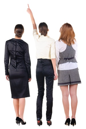 three beautiful young bussineswoman looking at wall. Rear view. Isolated over white. photo