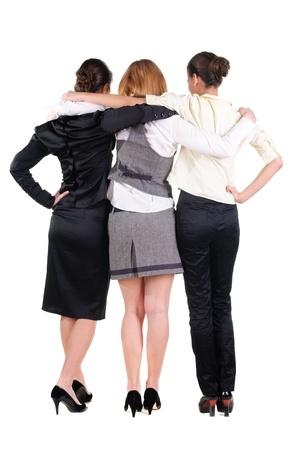 drie prachtige jonge bussineswoman kijken naar muur. Achteraanzicht. Geà ¯ soleerd op wit. Stockfoto