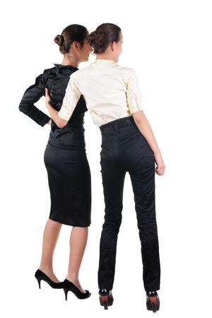 personas de espalda: Dos hermosos bussineswoman joven mirando la pared. Vista posterior. Aislado en blanco.