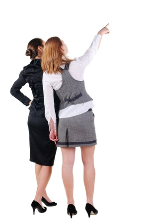 Two beautiful young bussineswoman looking at wall. Rear view. Isolated over white.