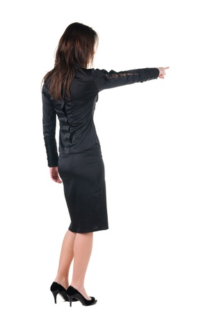 view from behind: Beautiful young woman pointing at wall. Rear view.