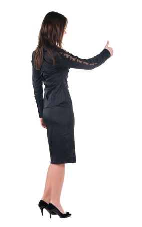 Beautiful young woman in dress gesture thumbs up. Rear view. Isolated over white. photo