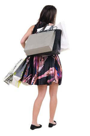 woman with shopping bags. rear view. isolated over white. photo