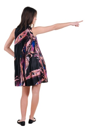 Beautiful young woman in dress pointing at wall. Rear view. Isolated over white. photo