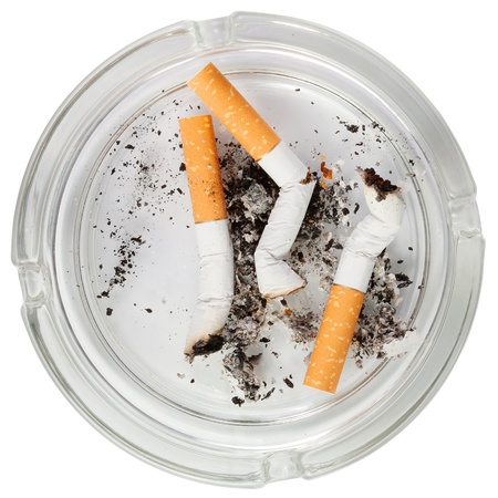 ashtray: Glass ashtray with stubs . Isolated over white background .