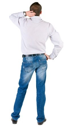 hands behind head: thoughtful young man. Rear view. isolated over white.  Stock Photo