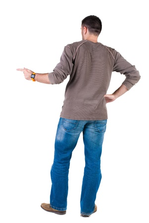view from behind: young man pointing at wall. rear view. Isolated over white .