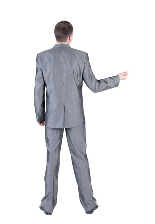 view of an elegant office: Businessman pointing at wall. rear view. Isolated over white .  Stock Photo