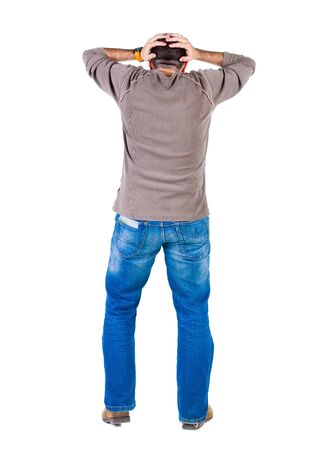 scared man: Back view of shocked and scared young  man. Holds hands upwards. Rear view. Isolated over white background. Stock Photo