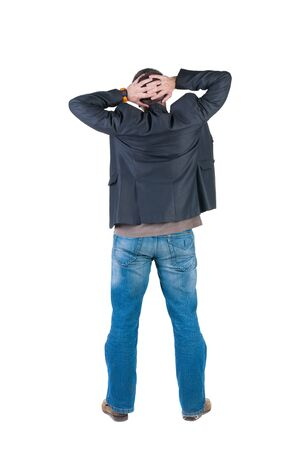 looking behind: Back view of shocked and scared young business man. Holds hands upwards. Rear view. Isolated over white background.